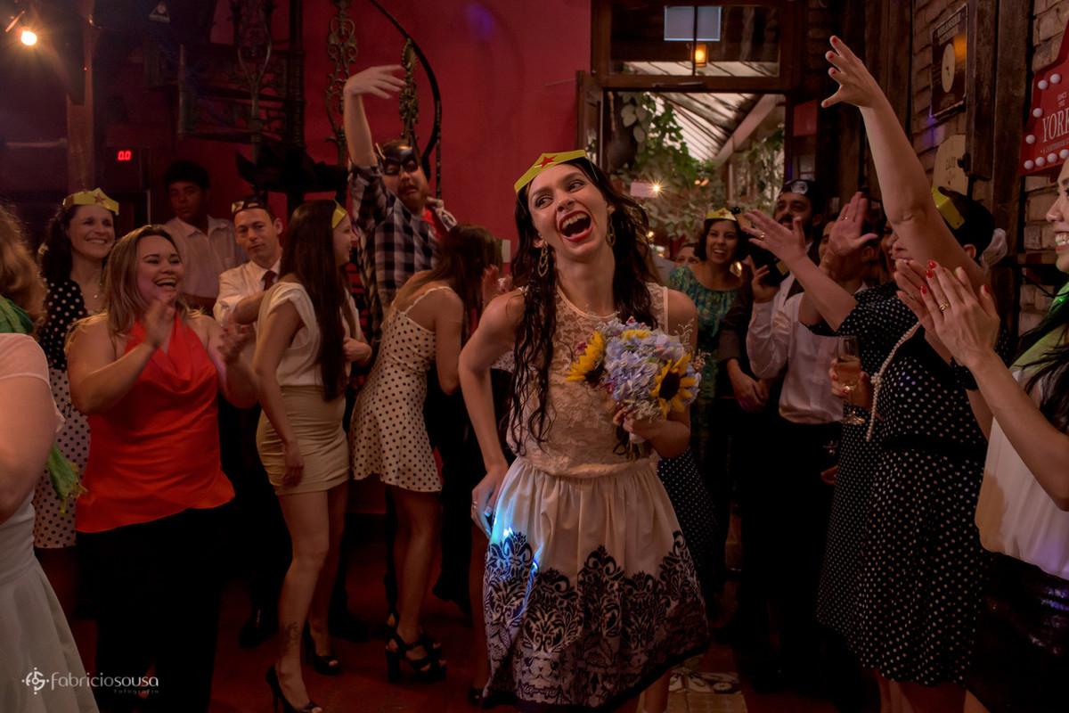convidada com máscara da mulher maravilha pega o buquet colorido