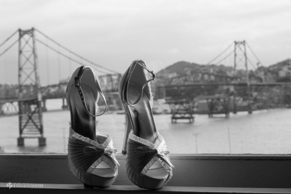 Sapato da noiva escorado na janela com ponte Hercilio Luz ao fundo preto e branco
