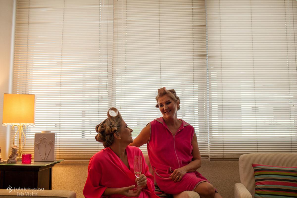 Filha e mãe conversam em casa com bobs nos cabelos