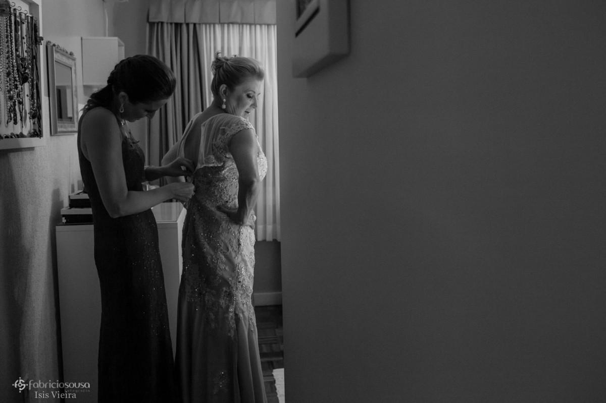Filha irmã da noiva ajuda a mãe a fechar o vestido