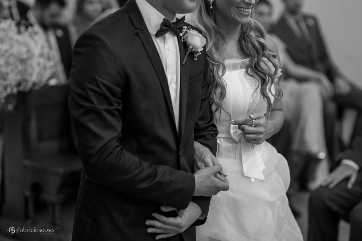 Detalhe dos noivos na igreja de braços entrelaçados