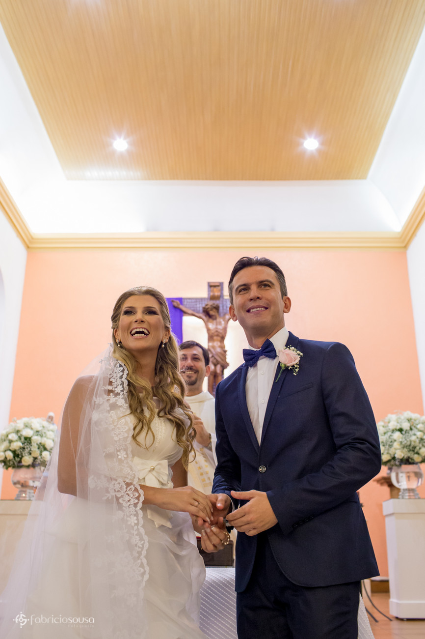 Casal de noivos no altar sorriem para os convidados presentes na igreja
