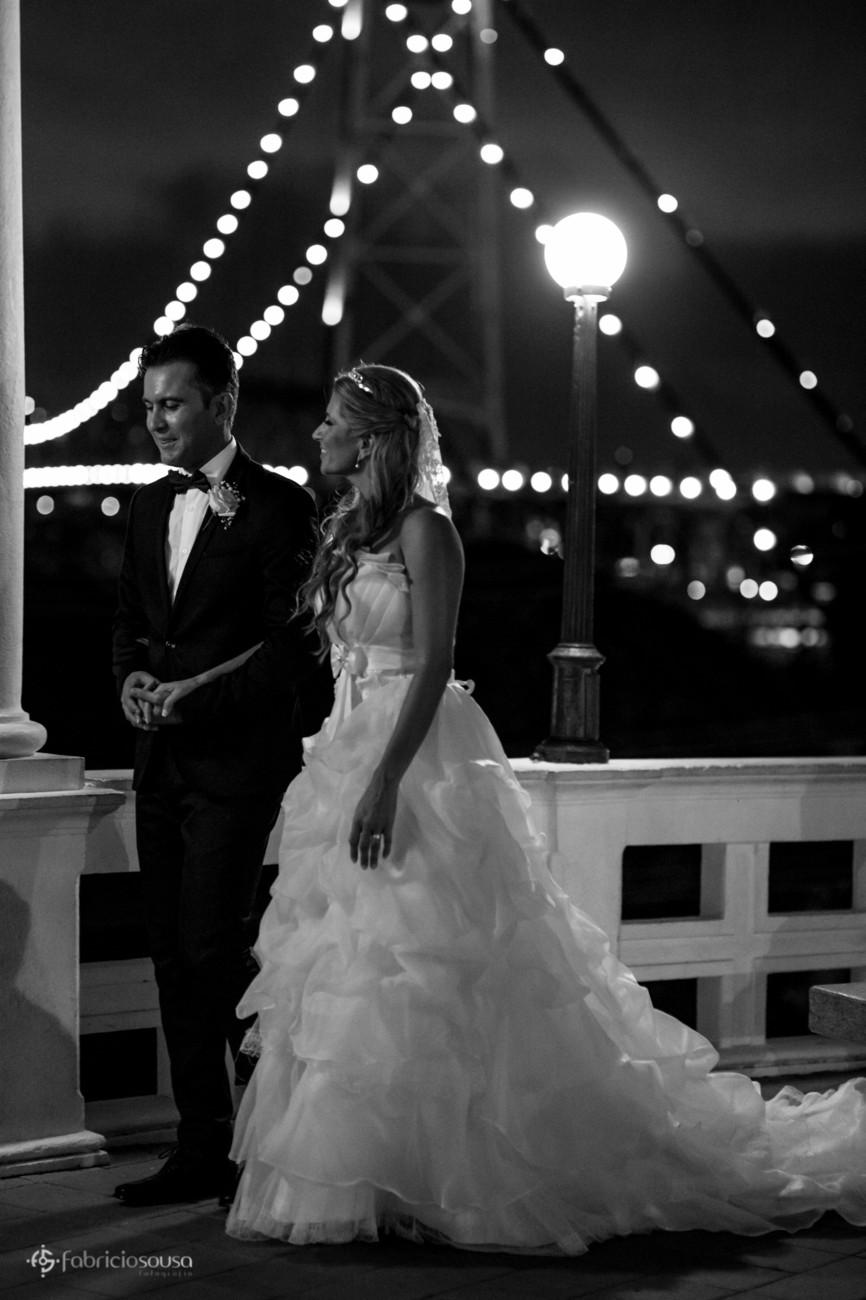Casal caminha com ponte ao fundo