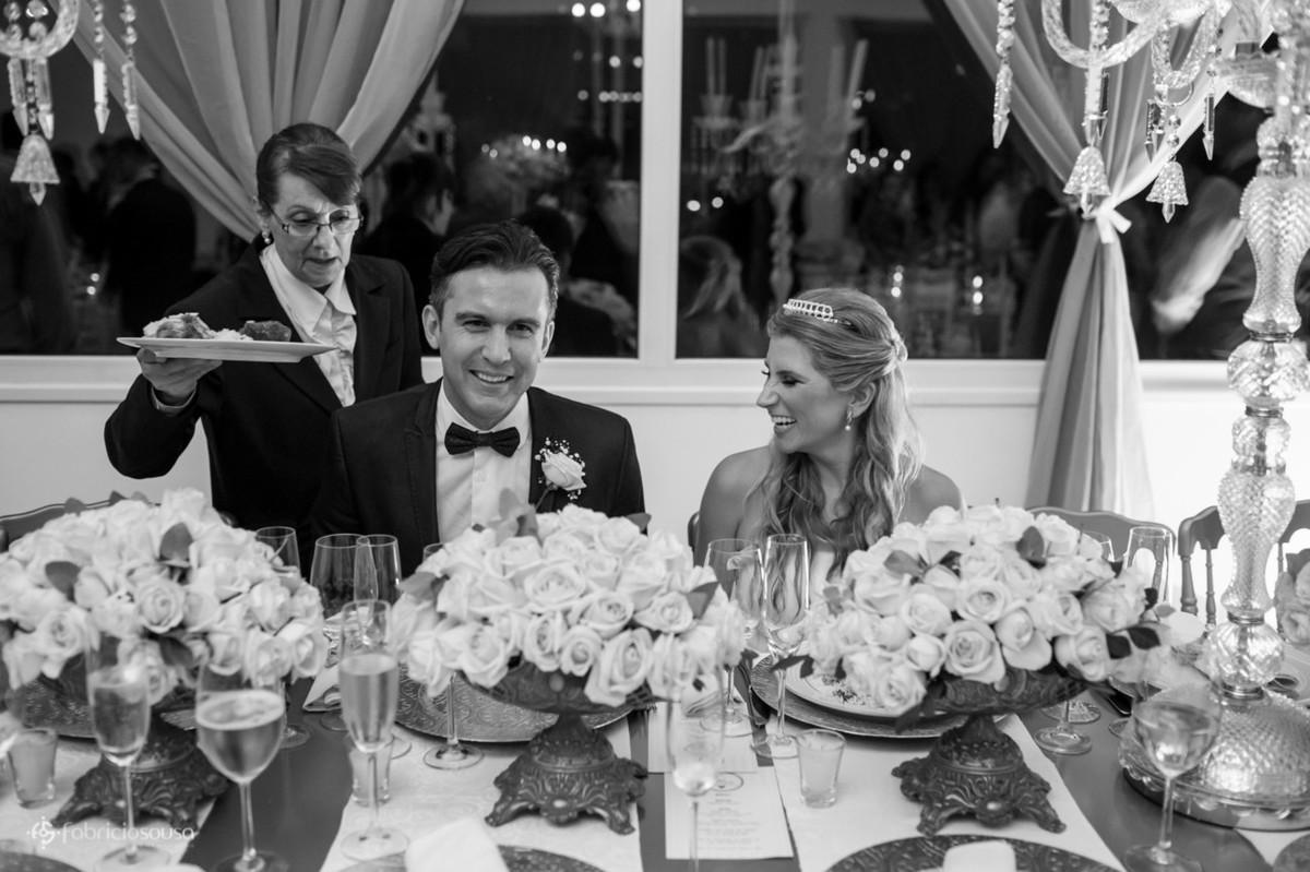 Casal de noivos sentados à mesa do jantar