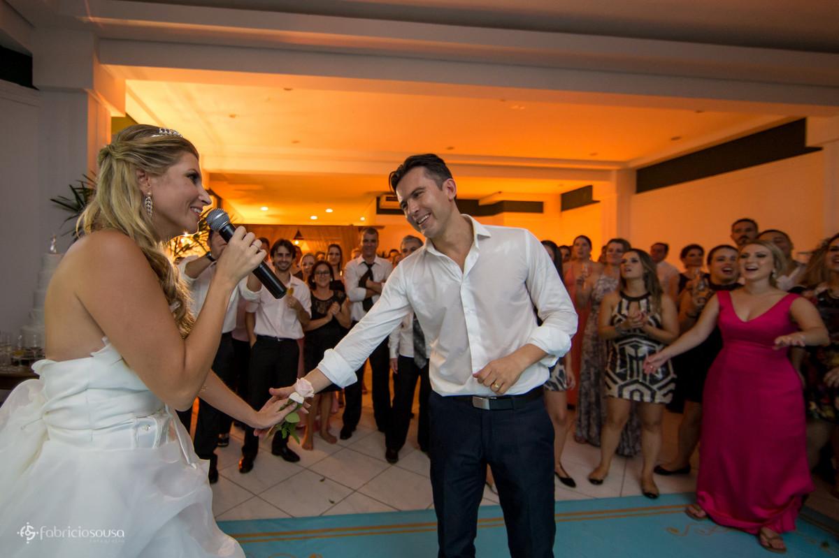 Noiva canta no microfone para o noivo