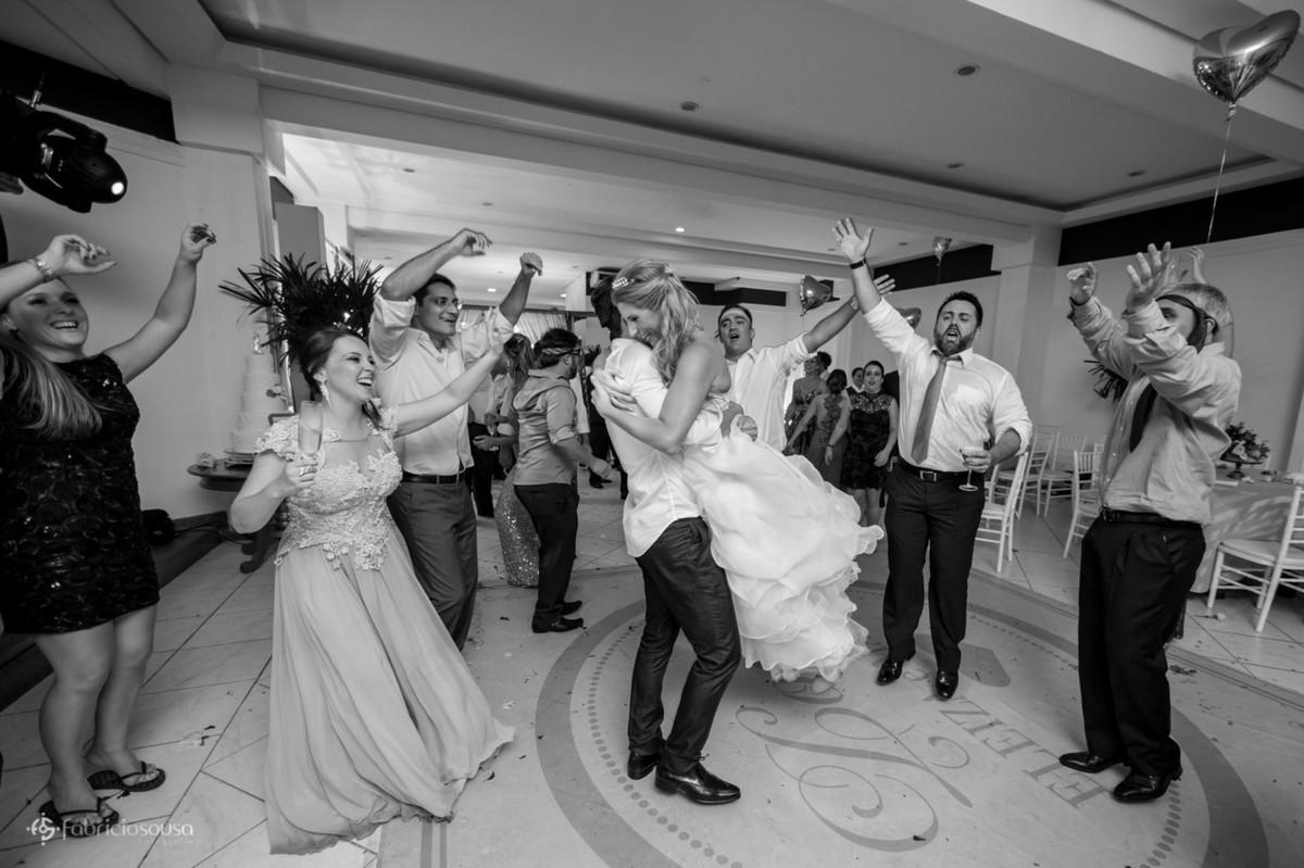 Noivo abraça e gira a noiva durante a festa de cerimônia na pista de dança com amigos em volta