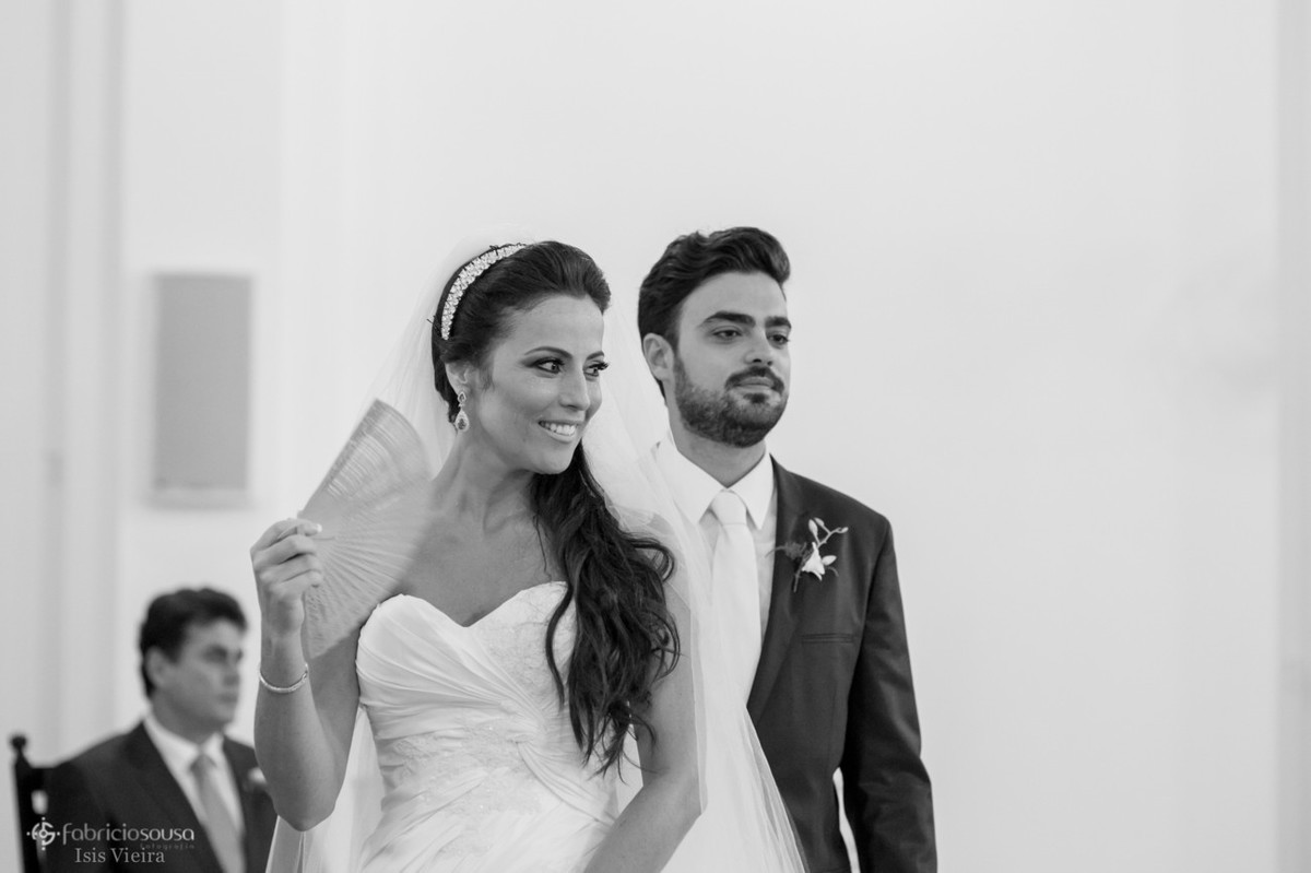 noiva se abanando com leque junto com noivo no altar
