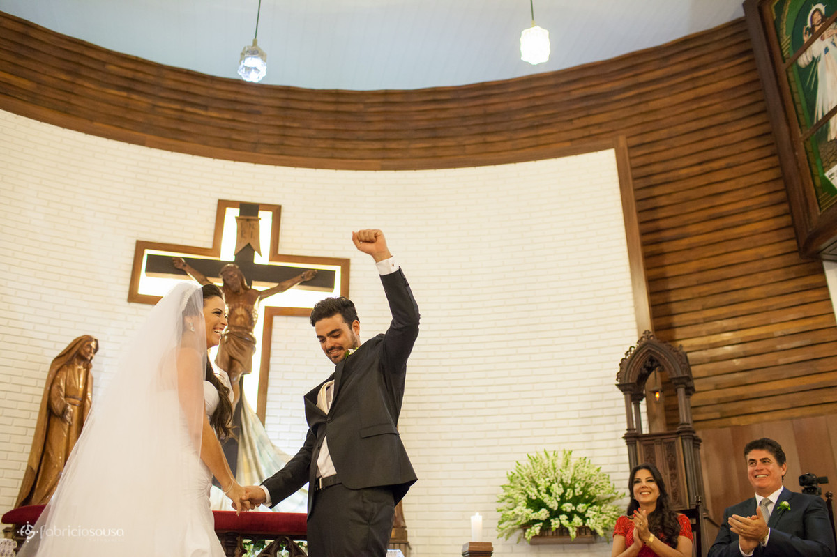 noiva sorri e noivo comemora logo após o primeiro beijo - pais assistem a cena divertida