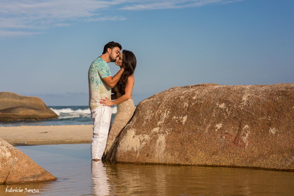 beijinho no rosto na praia encostados na pedra