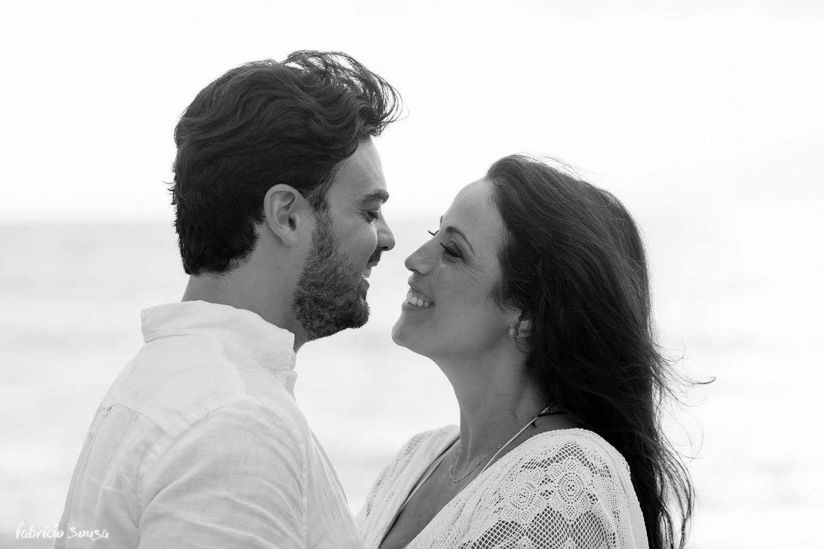 close do casal sorridente em ensaio fotográfico na praia