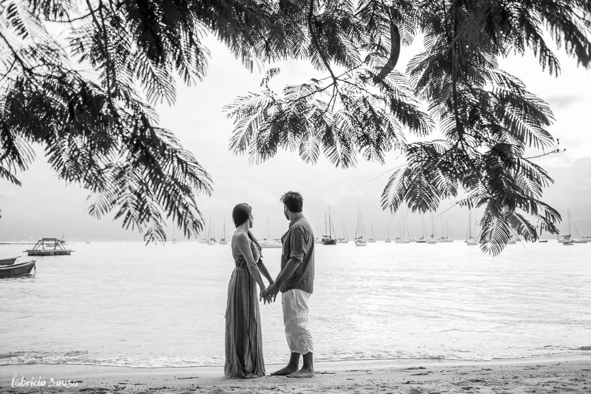 casal de mãos dados sob a arvore na praia de santo antonio de lisboa - final de tarde