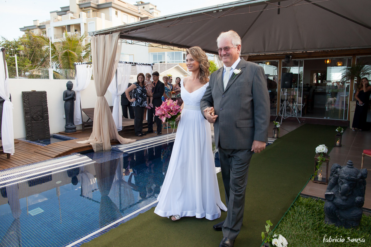 a noiva entrando com o pai na borda da piscina
