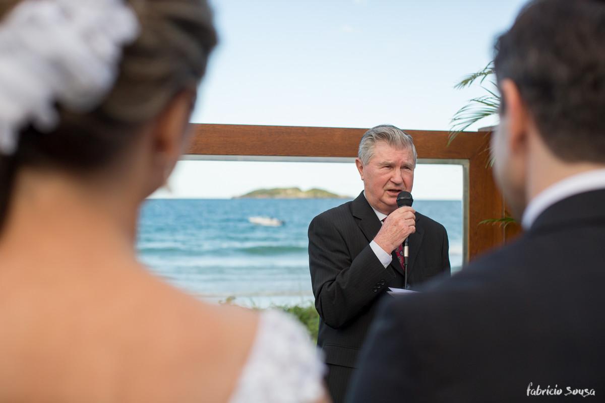 tio da noiva celebrando a cerimonia com o mar de fundo