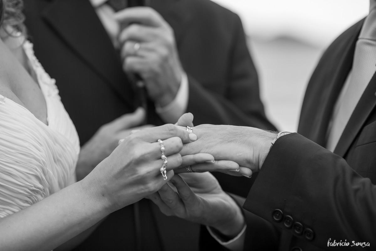 o detalhe das mãos colocando a aliança