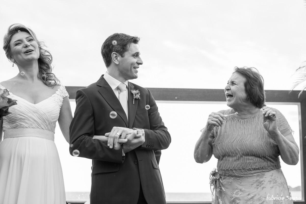 a mãe do noivo emocionada na saída com bolhas de sabão