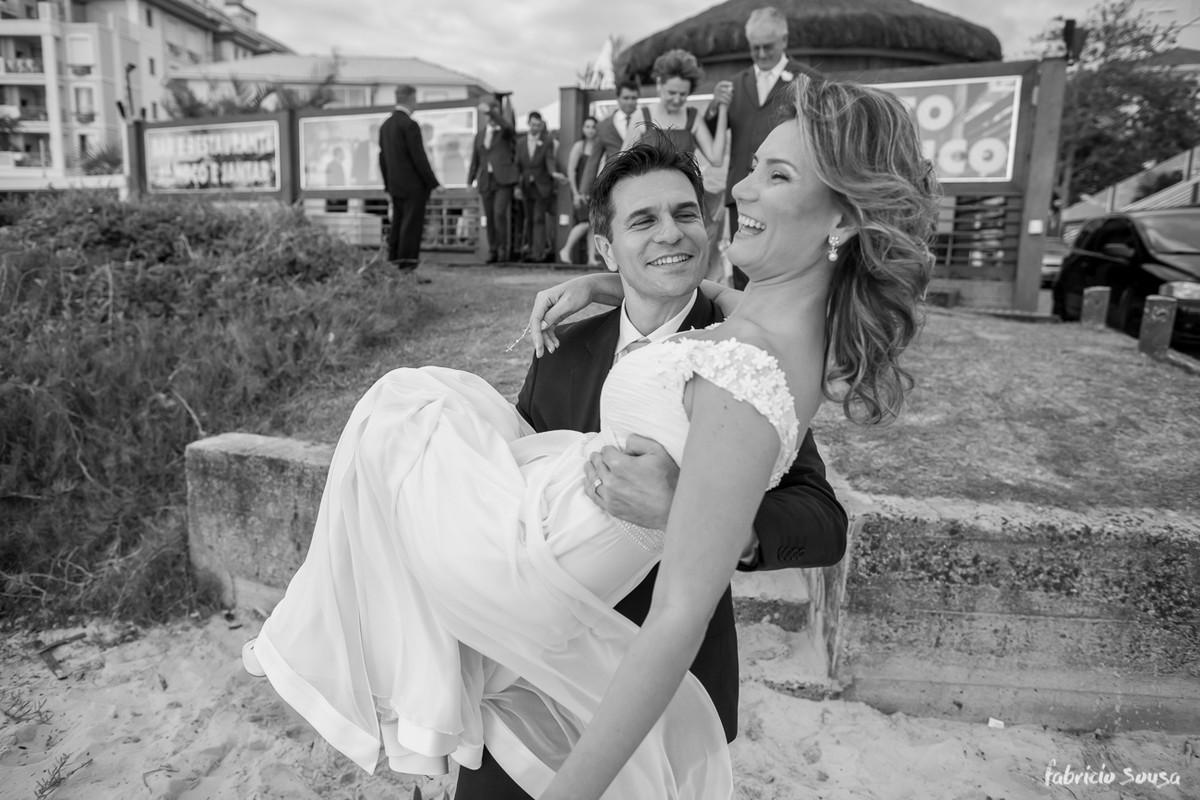 a noiva sendo carregada pelo noivo a caminho do mar na praia dos ingleses