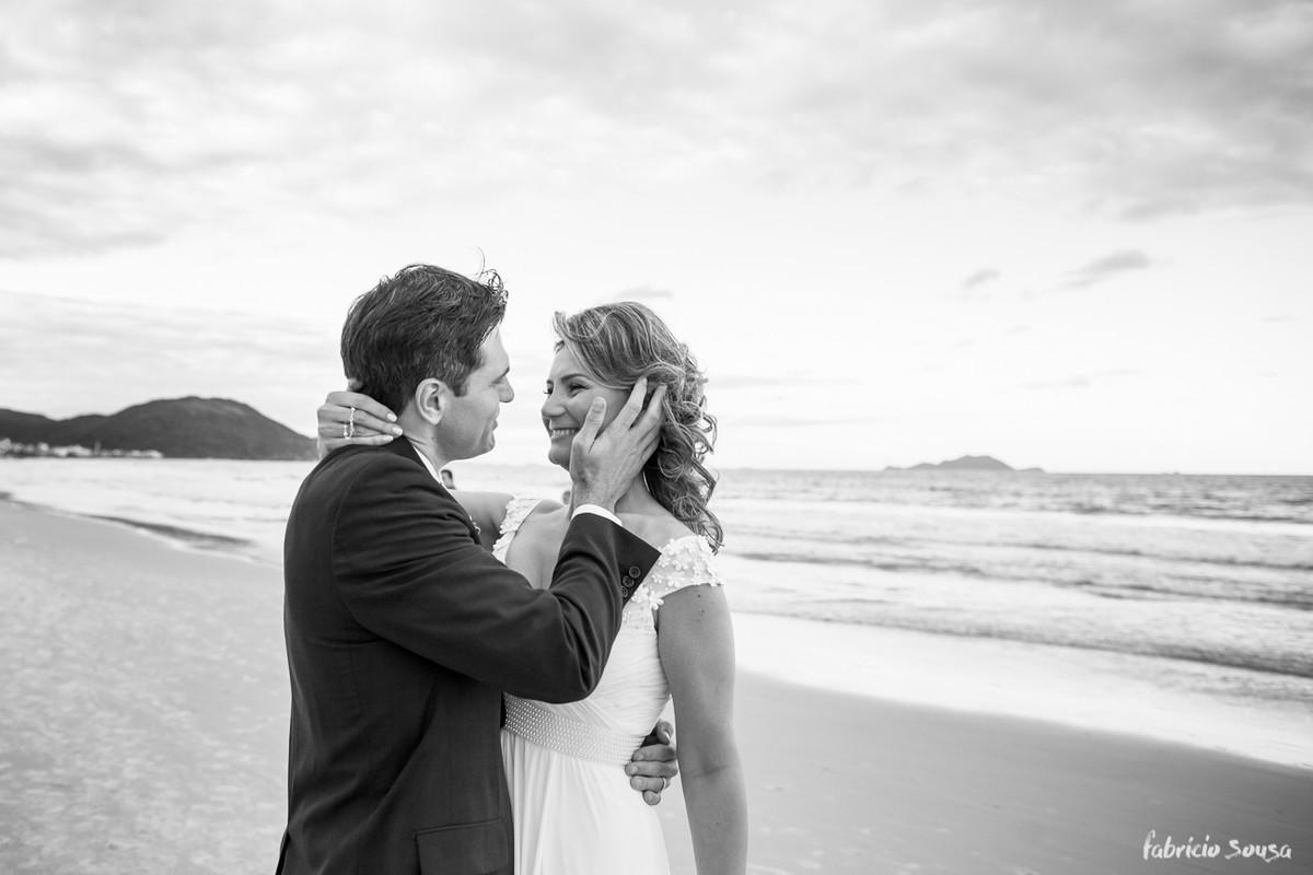 noivo acaricia a esposa na beira do mar