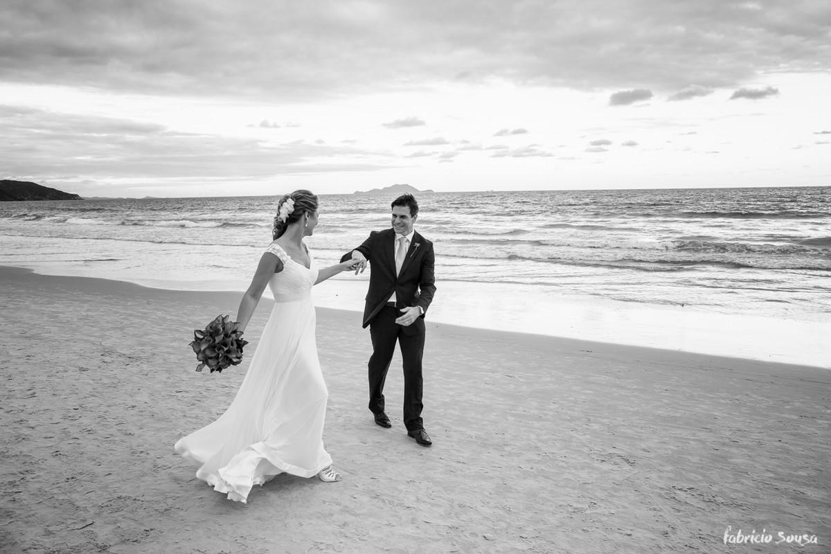 o noivos felizes dançando na areia da praia