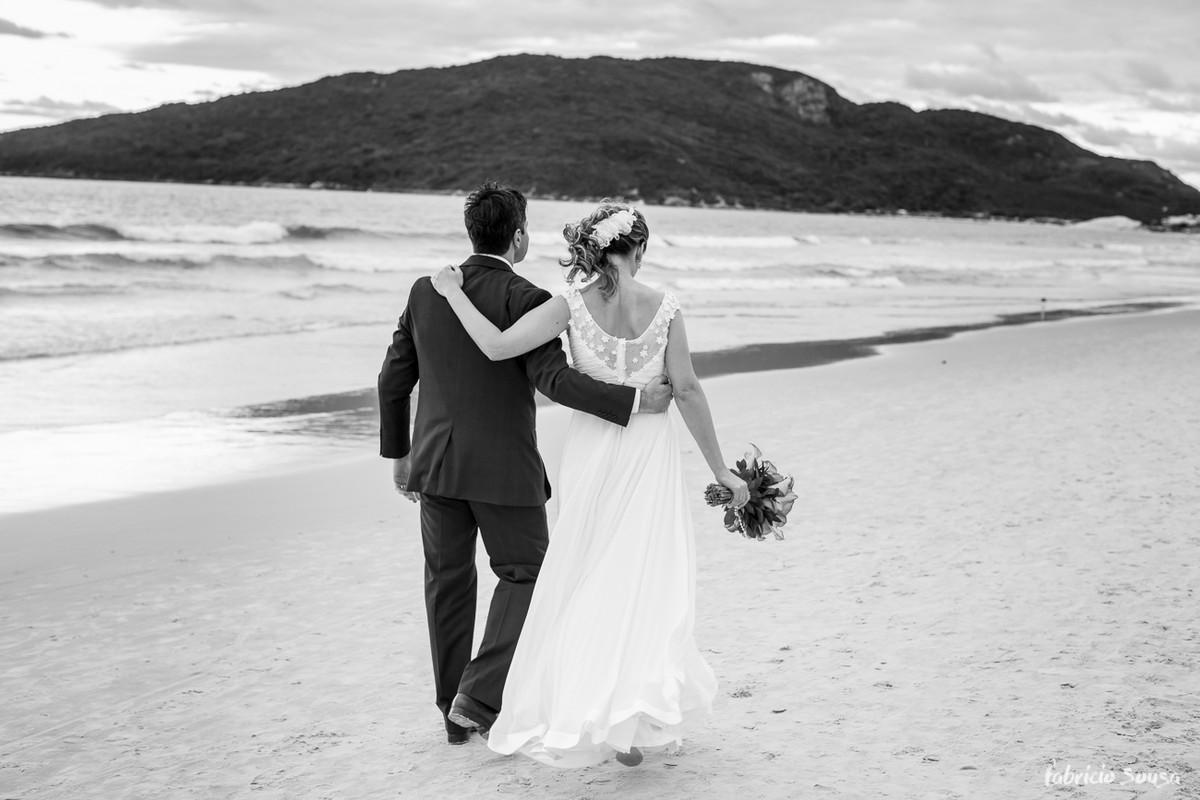 casal de noivos caminhando na praia dos ingleses em Florianópolis