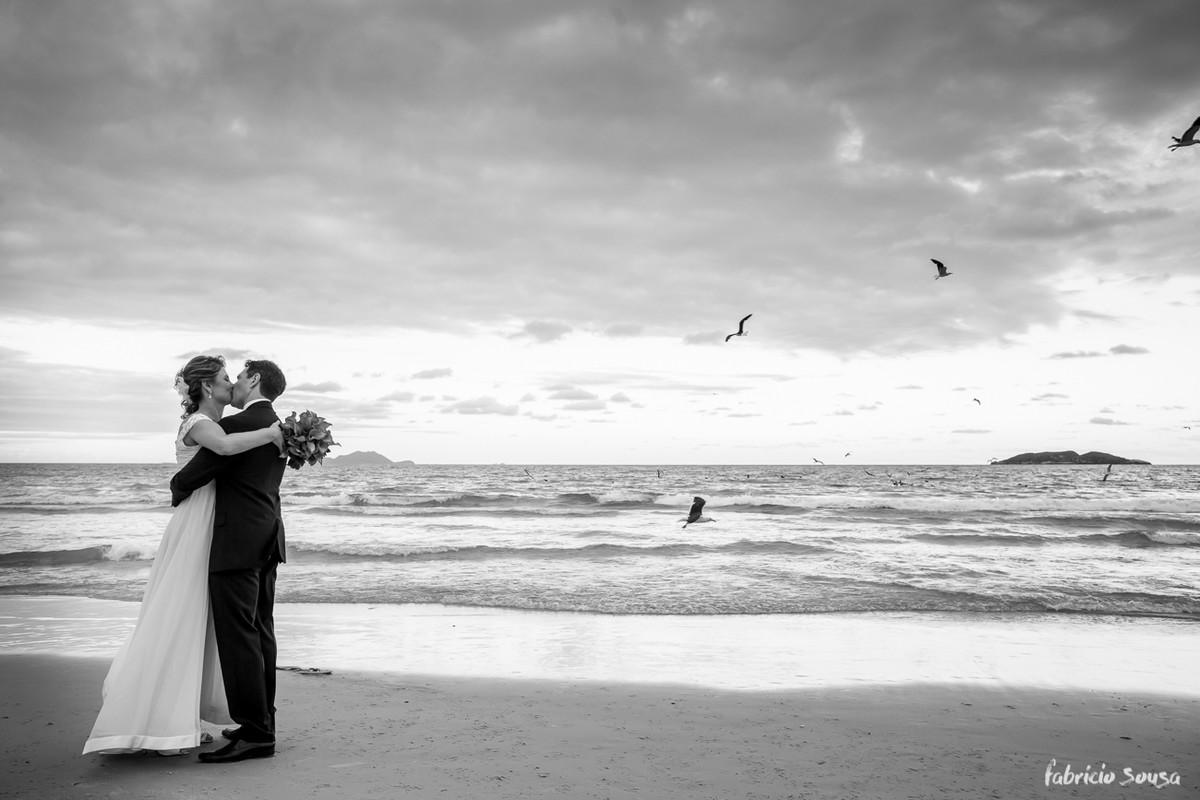beijo do casal de noivos com gaivotes sobrevoando a praia