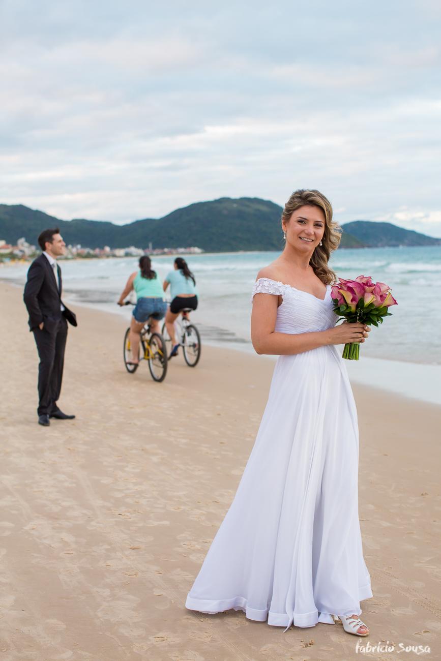 noiva com bouquet na praia - ciclistas passando na areia