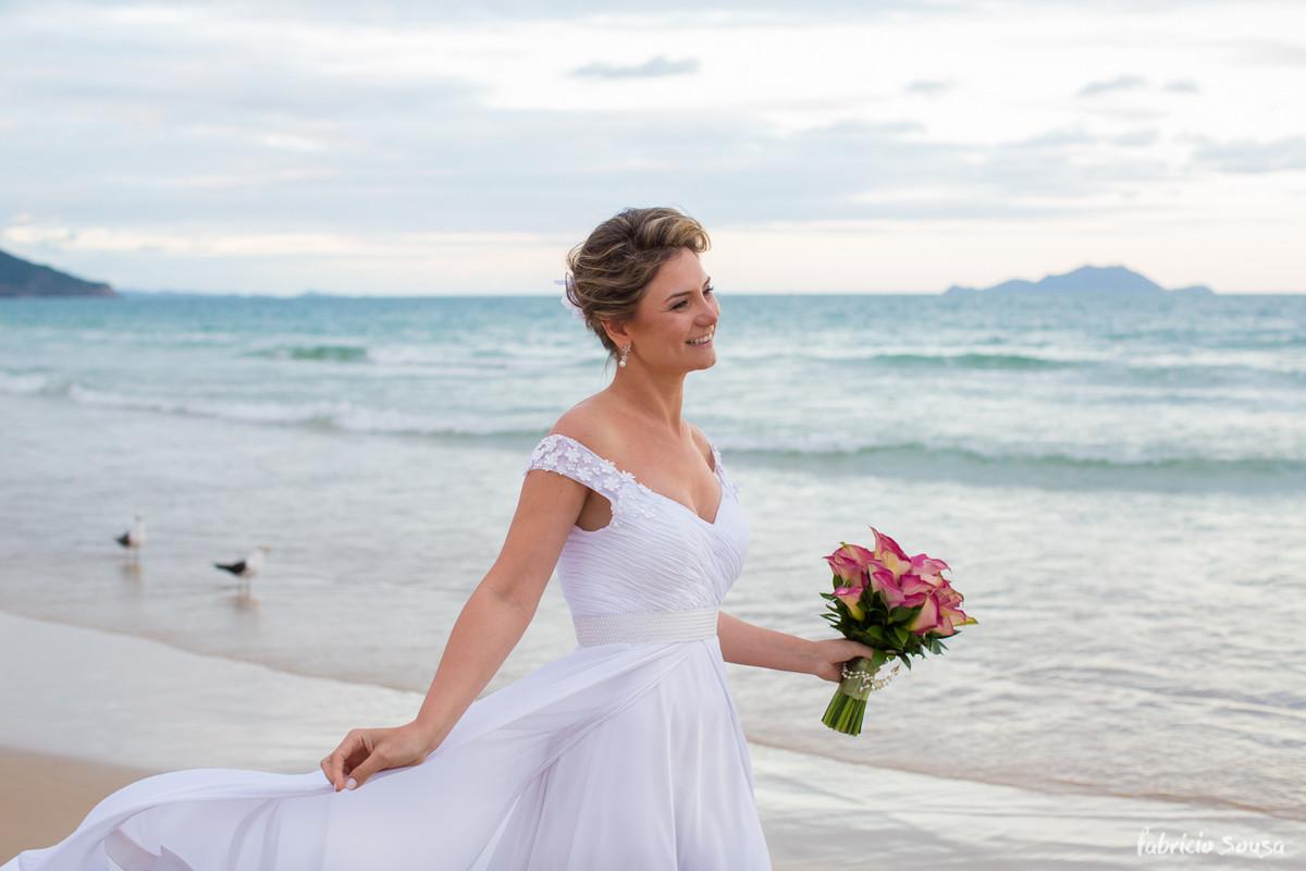 noiva maravilhosa segurando o vestido e o bouquet na beira do mar