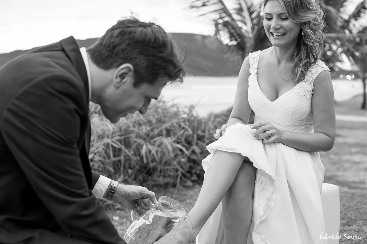 noivo lavando os pés da noiva após caminhada na praia