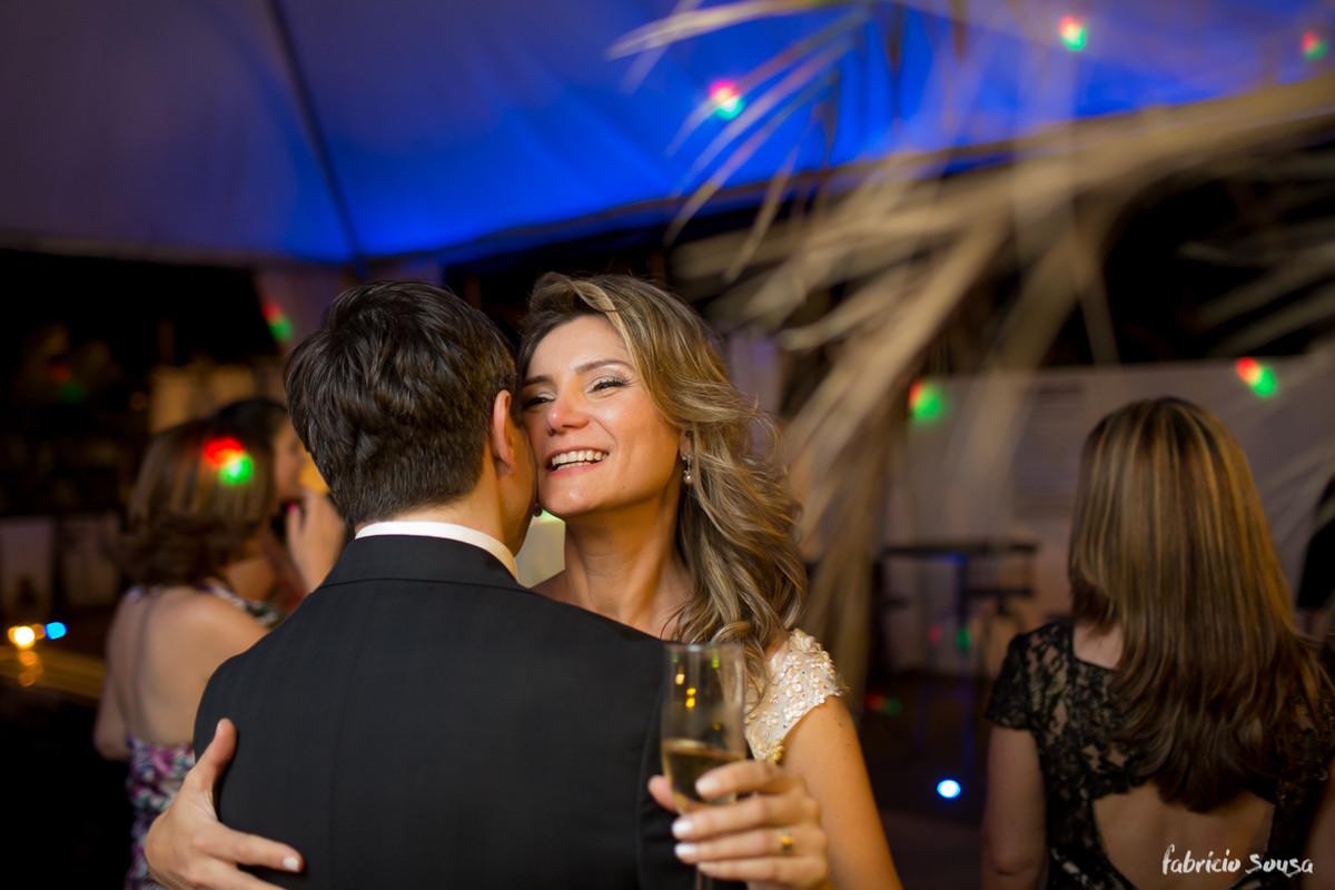 noiva sorridente tomando champagne e dançando na pista