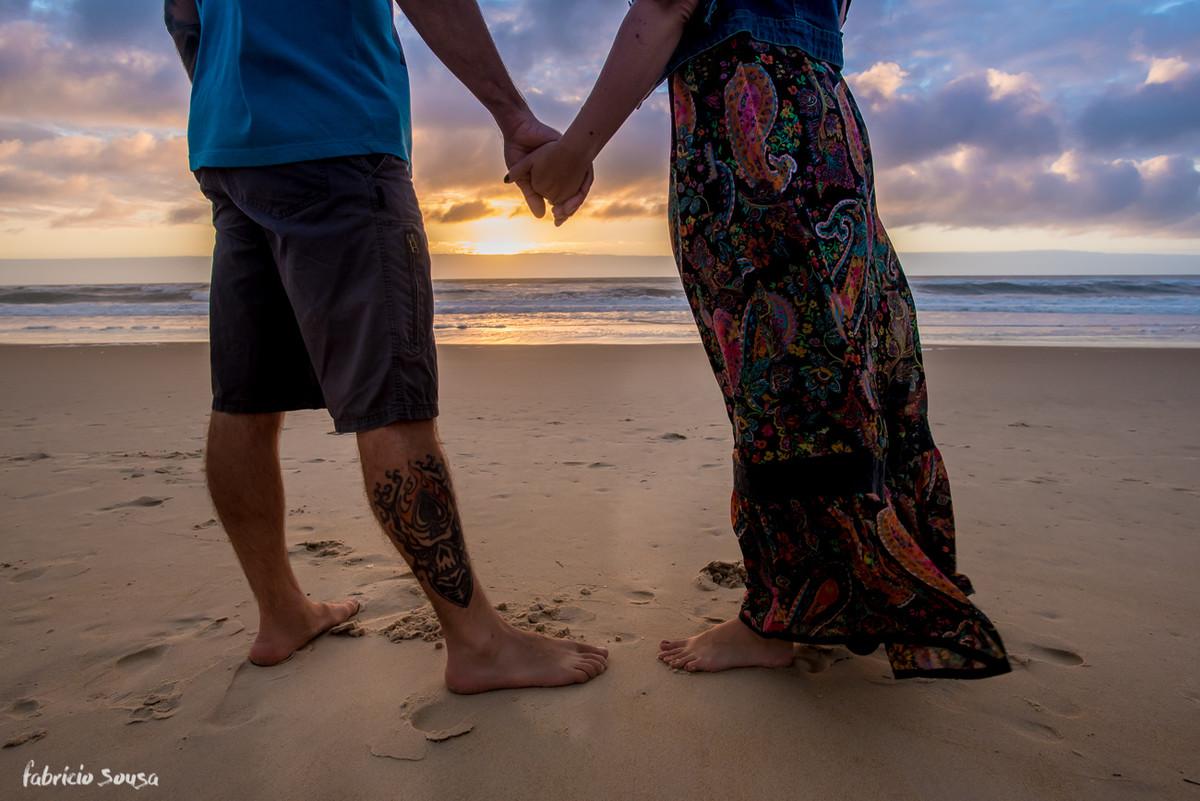 casal de mãos dadas no nascer do sol na praia em Floripa