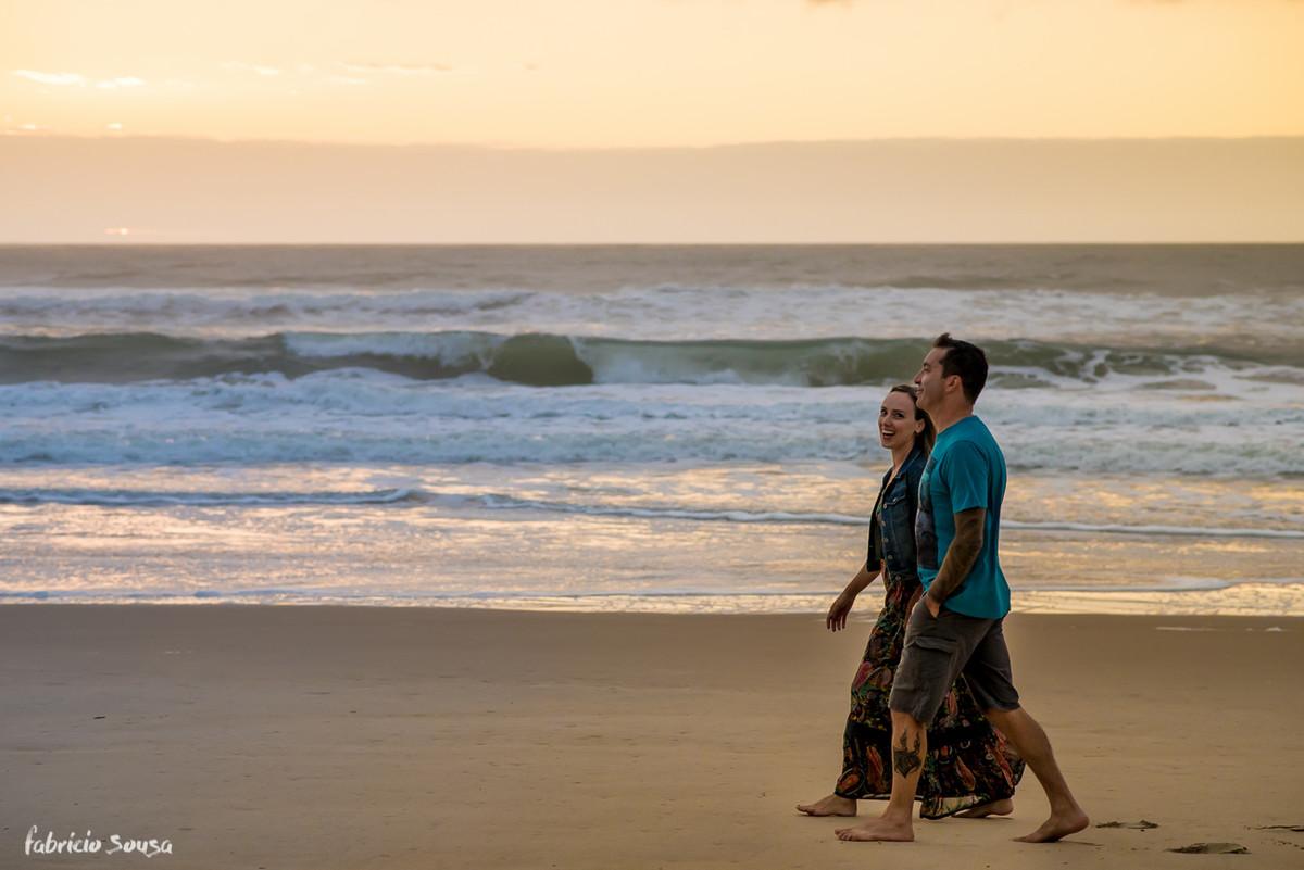 casal caminhando na areia da praia