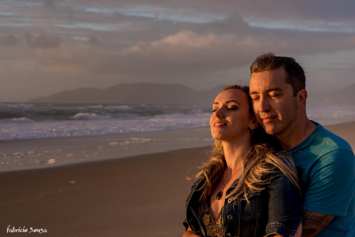 casal de olhos fechados sentindo os primeiros raios de sol do dia na praia do sul da ilha de Santa Catarina