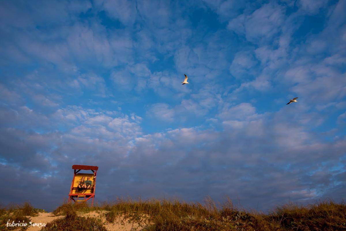 casal brincando na casa dos guarda-vidas com duas gaivotas passando no céu nublado