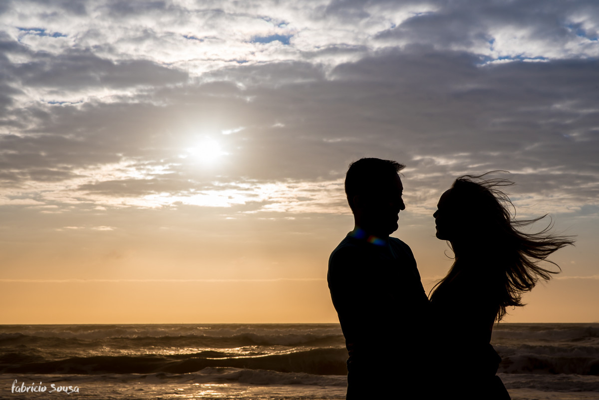 noivos se olhando em silhueta com mar e o sol nascendo no fundo