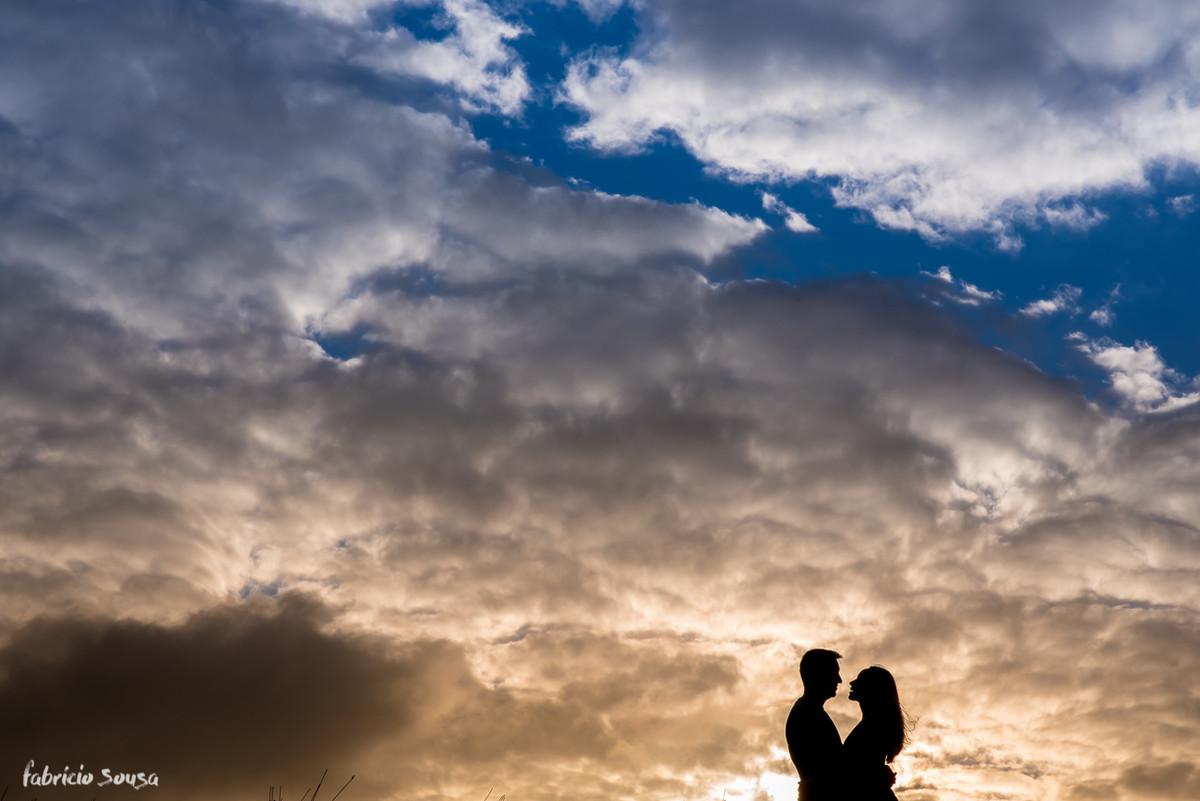 silhueta do casal quase se beijando com céu nebuloso