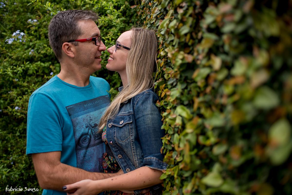 quase beijo do casal apoiado na cerca viva