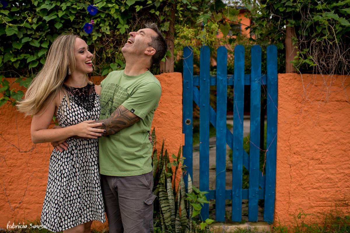 muitas risadas no ensaio pre-wedding em frente ao muro laranja e cerca azul