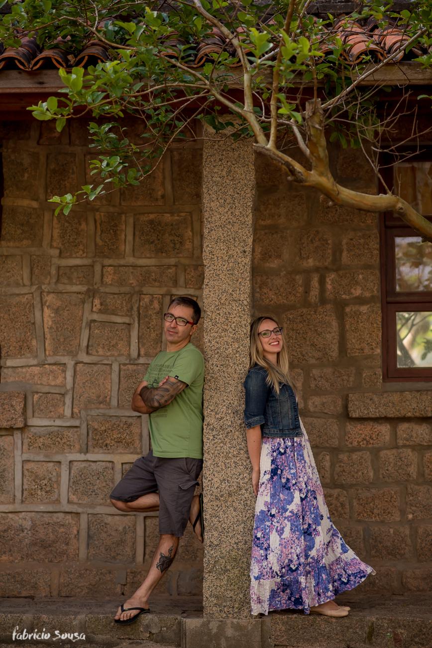 casal posa com muro de pedra e árvore singela no final do ensaio