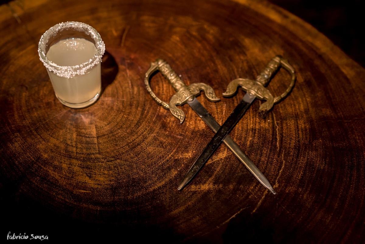 detalhe das espadas e shot de bebida no fundo de madeira rústica