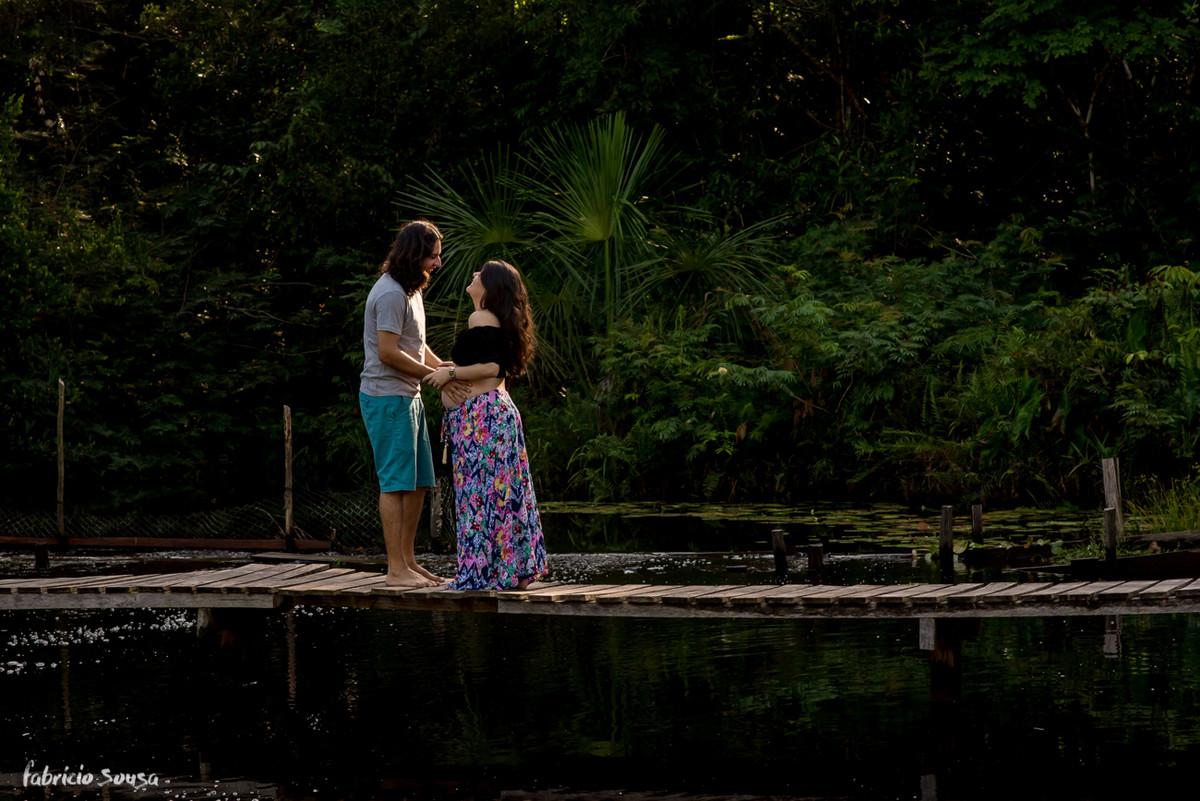 silhueta do casal gestante na ponte do balneário