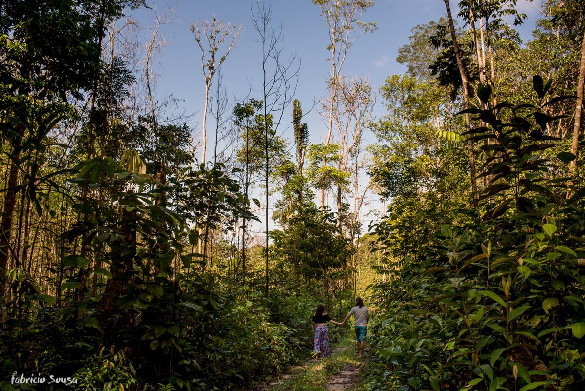 papai e mamae caminhando na trilha da floresta durante sessão fotográfica