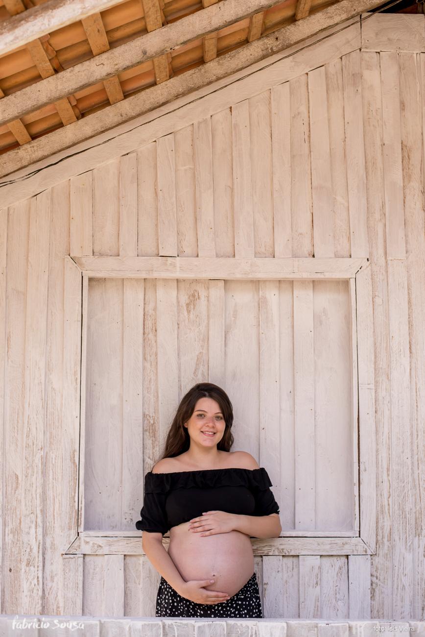 mamãe gestante segurando a barriga em frente a janela de madeira
