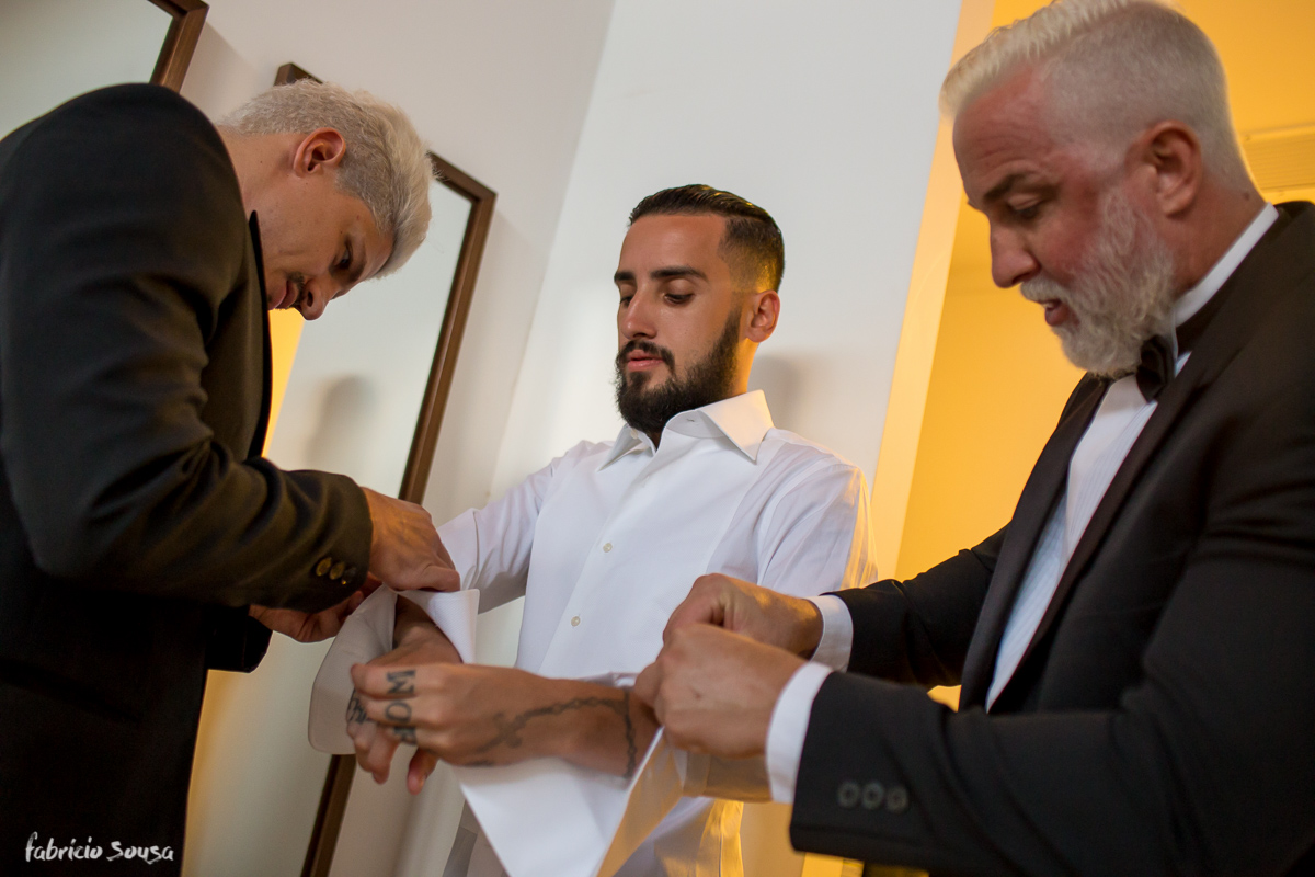 o noivo recebendo ajuda dos padrinhos para se vestir para seu casamento