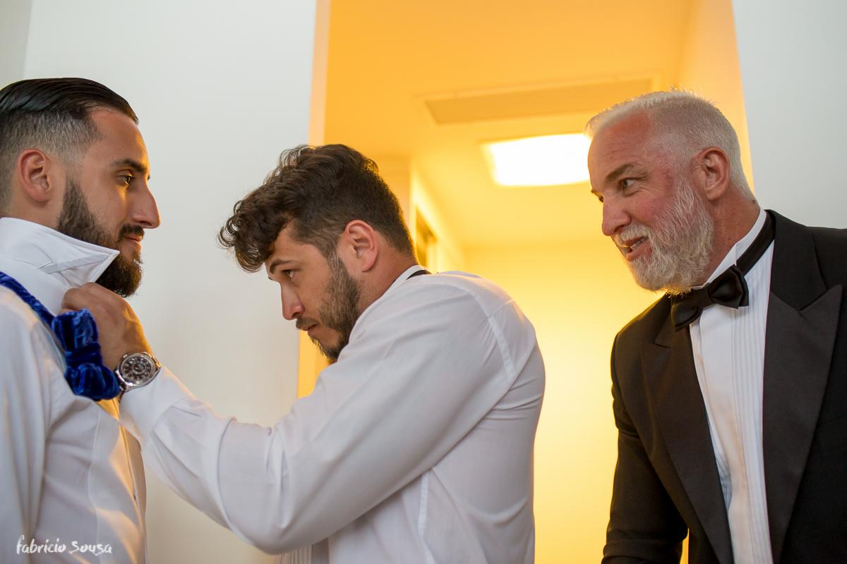 padrinho ajudando o noivo Giulliano a colocar sua gravata azul