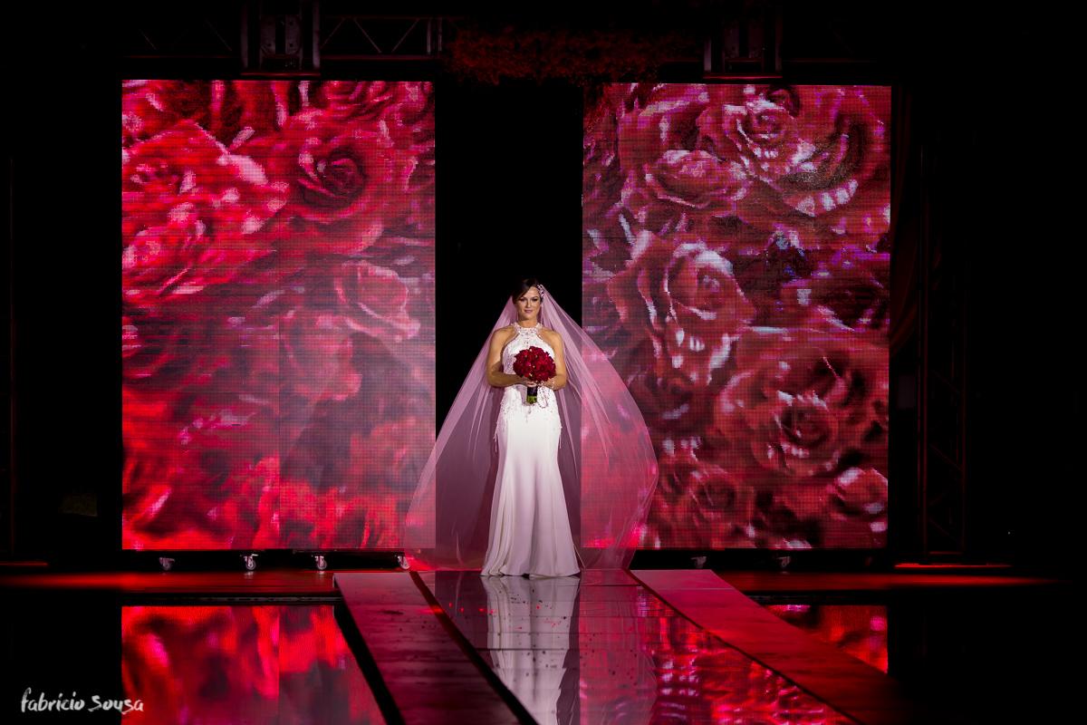 a entrada da noiva através do telão de LED com muitas rosas vermelhas