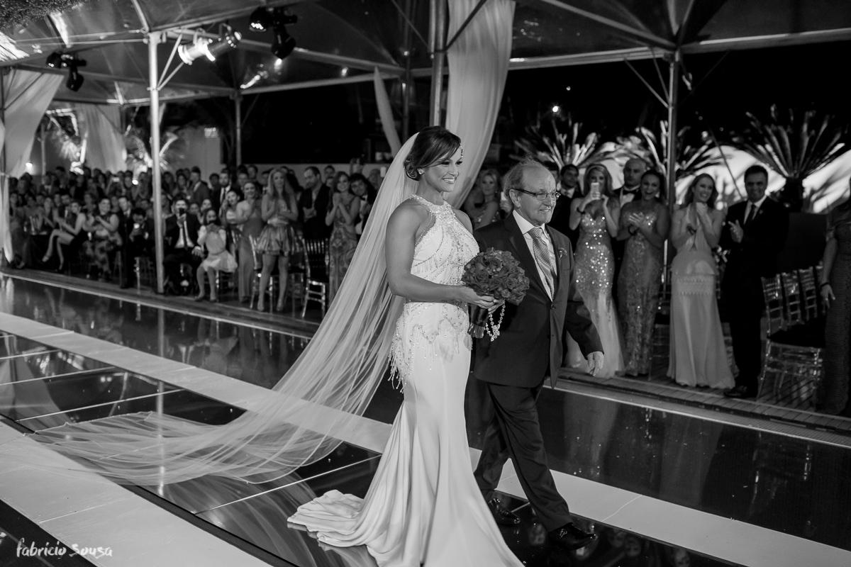 noiva caminha com seu pai para a cerimonia de casamento