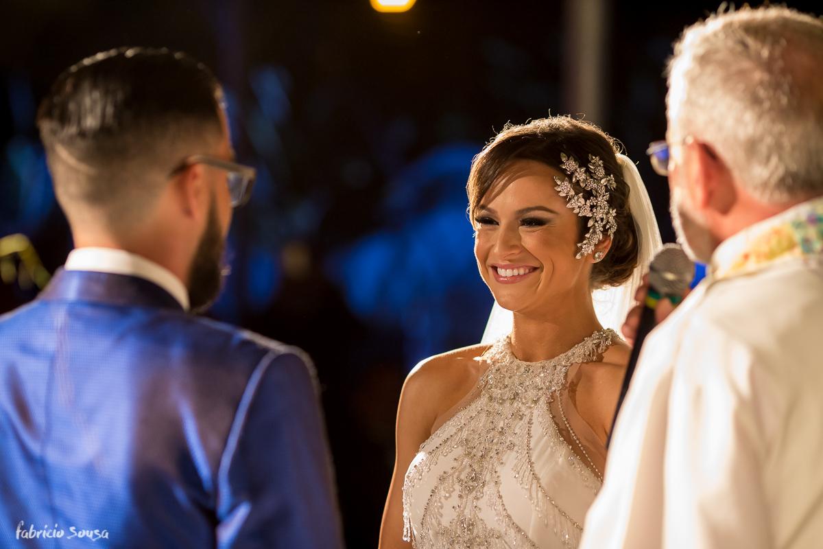 noiva Alice Matos sorri alegremente para seu amado no começo da cerimonia
