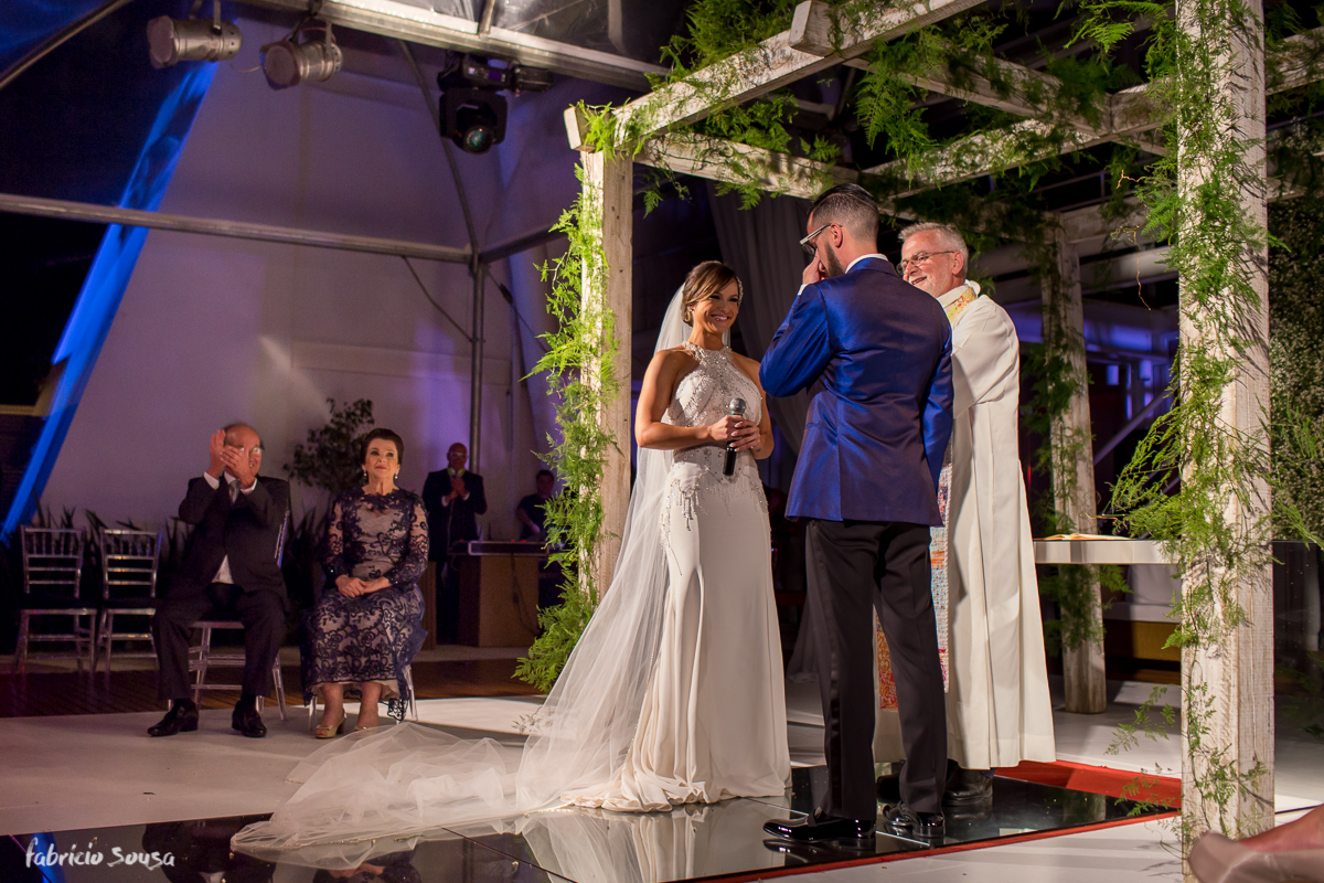 noiva termina seus votos e noivo se emociona no altar com celebração do Padre Prim