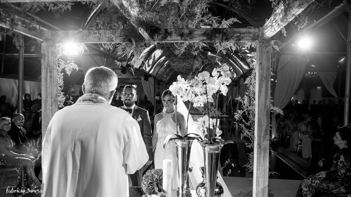 retrato preto e branco dos noivos no altar com orquídeas