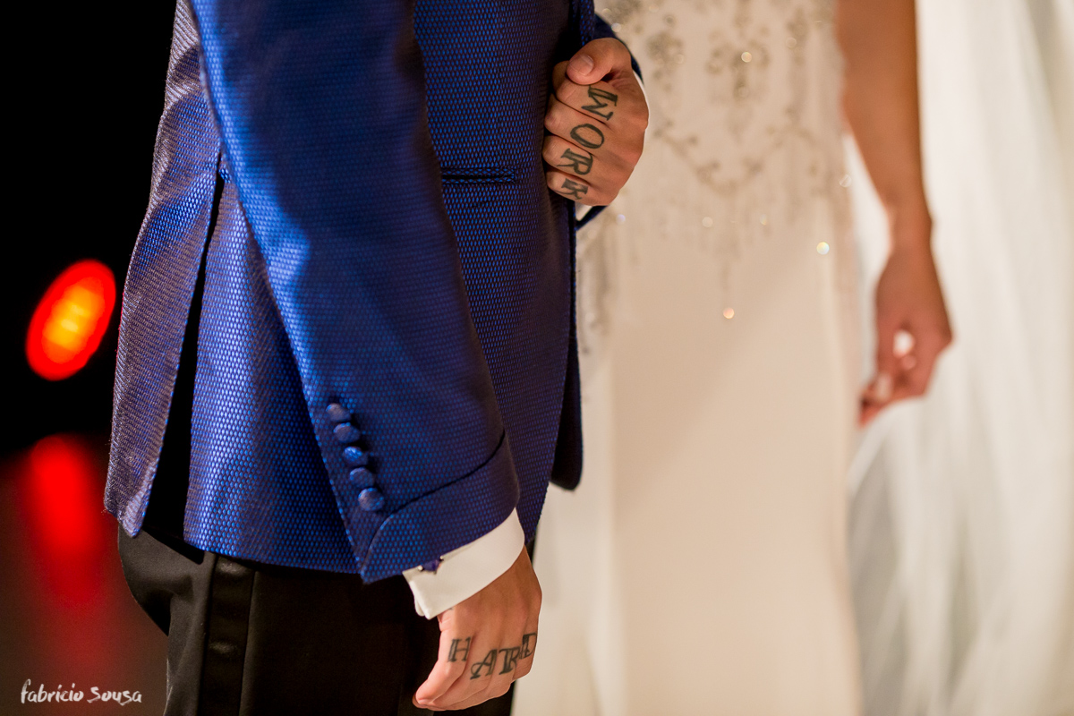 noivo tatuado Work Hard segura sua noiva no altar