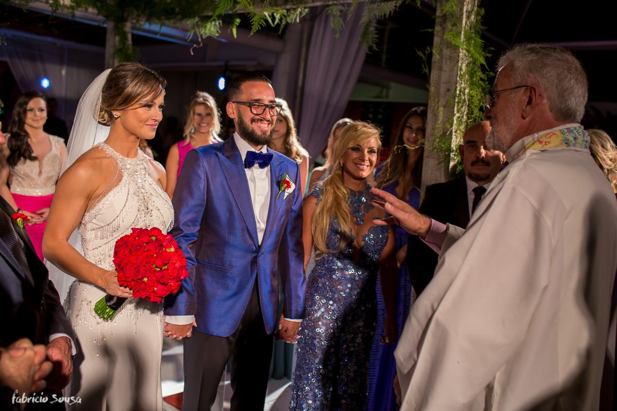 noivos felizes escutam as palavras do padre